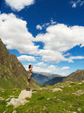 Facing the sun on the mountains. A girl on a big stone facing the sun on a summer mountain landscape. This picture is from Alps, in Italy Royalty Free Stock Images