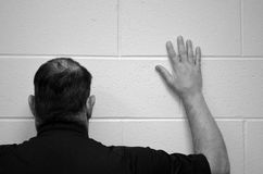 Facing the wall. Man with his face against the wall looking for a way out stock photography
