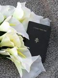 Fackbönbok och liljar Arkivfoto