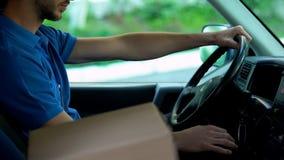 Facteur conduisant la voiture, position de boîte en carton près de lui, la livraison express de colis images stock