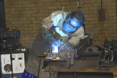 Factor worker welding closely. Artisan welding closely, concentrating on intricate work. Shows the blue hue from the bright arc reflecting off the helmet as the Stock Photography