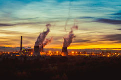 Factories at night, the silhouettes of the pipe producing a noxious smoke into the sky.. stock photo