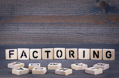 Factoring word written on wood block. Dark wood background with texture royalty free stock photo