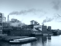 Factory. A factory in an industrial area with a river and cargo ships in the front royalty free stock photo