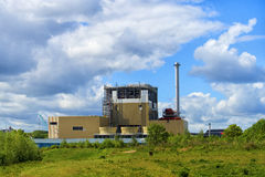 Factory against blue cloudy sky. Closeup of factory against blue cloudy sky Royalty Free Stock Image