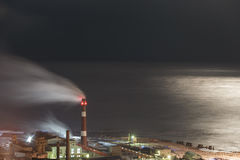 Factory against the sea in the moonlight stock photo