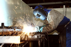 Factory Artisan welding. Factory worker wearing protective gear, welding on a production line Royalty Free Stock Images