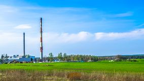Factory on the background of fields and blue sky.  stock images