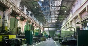 Factory beam crane moves on top of a large workshop. Workers at turning lathes ding metal processing at plant and move stock video footage