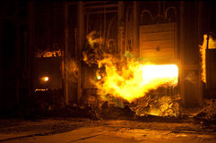 Factory blast furnace. Hot flames billowing out of a large factory blast furnace royalty free stock photo