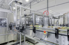 Factory for bottling beverages in cans. Conveyor belt in motion at production and bottling of drinks in tin cans. production and bottling of drinks in tin cans Stock Images