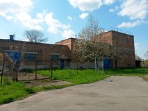 Factory brick building abandoned and without people during spring blossom of trees, on background blue sky with clouds. Image stock photo
