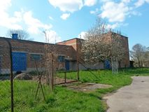 Factory brick building deserted and without people during spring blossom of trees, on background blue sky with clouds. Image royalty free stock images