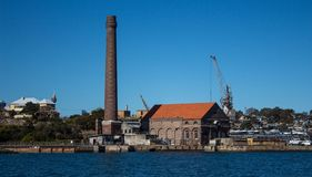 Free Factory Brick Smoke Stack At Historic Dockyard And Boat Storage With Crane Against Blue Sky Set On Cockatoo Island Sydney Harbour Stock Photos - 150213003