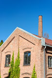 Factory Building and Chimney. Old factory building on clear polarised blue sky with a chimney behind Royalty Free Stock Image