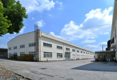 Factory building. Exterior with blue sky and white clouds Royalty Free Stock Photo
