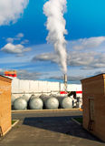 Factory with a chimney. And white smoke against cloudy sky Royalty Free Stock Image