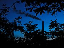 Factory chimney. The factory chimney behind trees Royalty Free Stock Photo