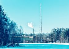Factory chimney and the steam in winter countryside at Finland. Lapland stock photos