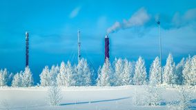Factory chimney and the steam in winter countryside Finland, Lapland. Factory chimney and the steam in winter countryside, Finland, Lapland stock images
