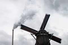 Factory chimney and wind mill Royalty Free Stock Image
