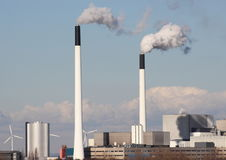 Factory chimneys with clouds and small windmills Stock Photography