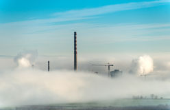 Factory chimneys and clouds of steam. Blue sky royalty free stock images