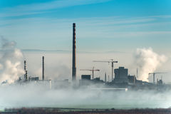 Factory chimneys and clouds of steam Royalty Free Stock Photo