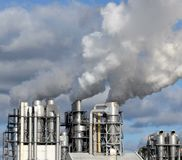 Factory chimneys with emissions. A steel chimney of a factory or plant with smoke or water vapor emissions royalty free stock photo