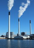 Factory chimneys at energy plant with blue sky and Stock Photography