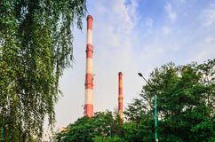 Factory chimneys producing electricity. Red and white industrial chimneys royalty free stock photo