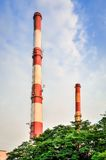 Factory chimneys producing electricity. Red and white industrial chimneys stock images