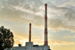 Factory chimneys producing electricity. Red and white industrial chimneys royalty free stock photography