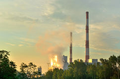 Factory chimneys producing electricity. Red and white industrial chimneys royalty free stock image