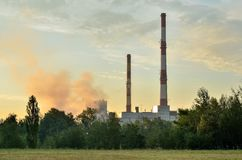 Factory chimneys producing electricity. Red and white industrial chimneys stock photography
