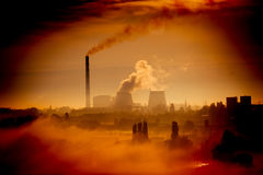 Factory with chimneys and smoke in the orange glare of dawn Royalty Free Stock Photo