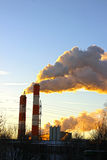 Factory chimneys smoke rising into the sky Stock Images