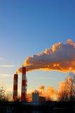 Factory chimneys smoke rising into the sky Stock Photos