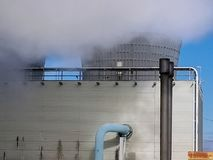 Factory with cooling tower and steam. Steam rising out of industrial factory cooling tower with blue sky background stock photos