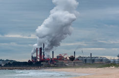 Factory discharging steam in the afternoon. Steam emission from a factory stock image