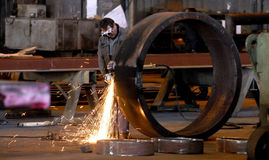 Factory. Electric wheel grinding on steel structure in factory Stock Images