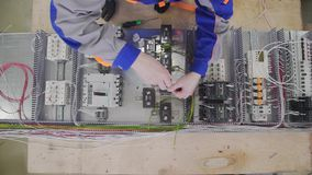 Factory electrical cabinet assembly using a hand screwdriver in factory stock footage