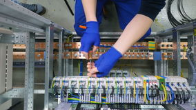 Factory electrician engineer installing cables with screwdriver, tighten the nut in electical box control cabinet into