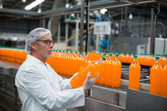 Factory engineer examining a bottle of juice Stock Image