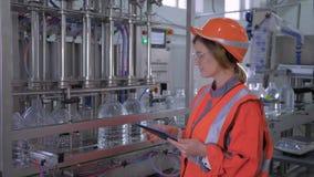 Factory engineer female into helmet uses digital tablet to control work of belt line for bottling water in bottles at stock video footage