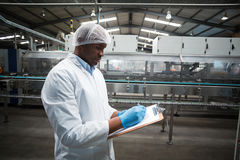 Factory engineer maintaining record on clipboard in factory. Factory engineer maintaining record on clipboard in drinks production plant Royalty Free Stock Images