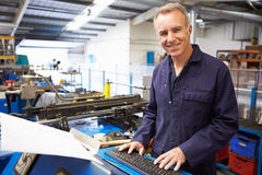 Factory Engineer Operating Hydraulic Tube Bender. Smiling At Camera royalty free stock photo