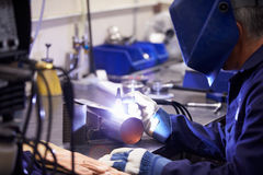 Factory Engineer Operating TIG Welding Machine. Wearing Protective Clothing And Mask Stock Photo