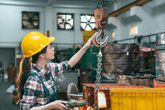 Factory female worker adjusting chain cranes. Beautiful young industry factory female worker adjusting chain cranes machining when she ready to transport lathe royalty free stock photos