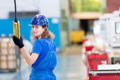 Factory female worker operating workshop gantry crane. Woman worker operating workshop gantry crane at manufacture workshop Royalty Free Stock Photography